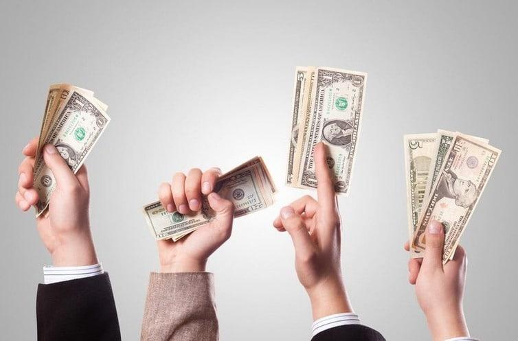 Il y a 4 mains qui se tendent vers le haut avec plusieurs billets vert en dollars dans la main